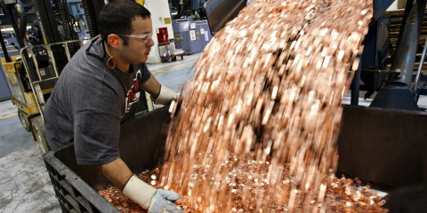 UNITED STATES - AUGUST 08: Mike Spinosa, a pit driver at the U.S. Mint, transfers one cent blanks before they are struck into pennies in Philadelphia, Pennsylvania on Wednesday, Aug. 8, 2007. The dollar fell to a record low against the euro after Federal Reserve policy makers cut their benchmark interest rate by a quarter-percentage point. (Photo by Stephen Hilger/Bloomberg via Getty Images)